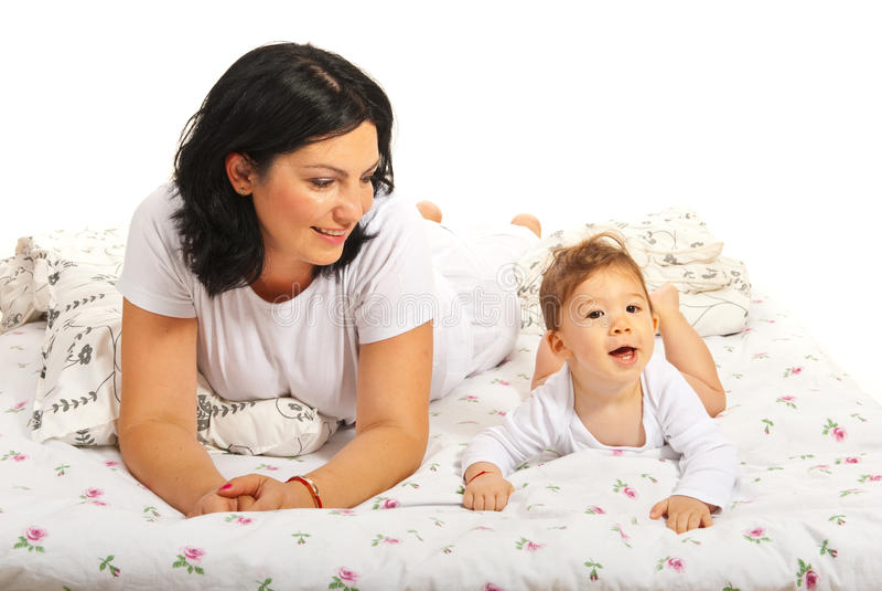 Mamá feliz con el hijo del bebé en cama foto de archivo libre de regalías