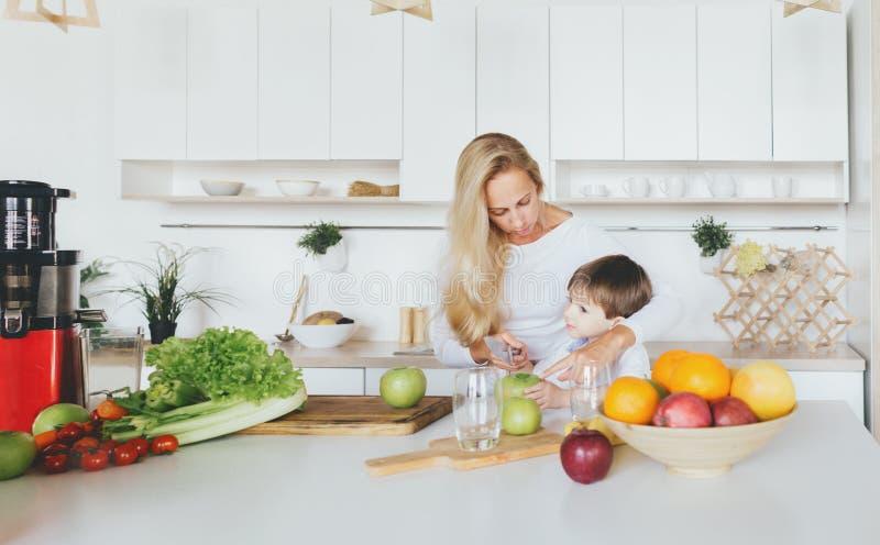 Mamá feliz del niño de la familia que cocina el hogar del desayuno en la cocina imagen de archivo