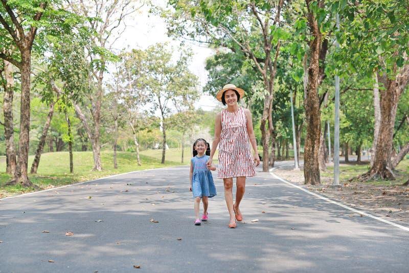 Mamá feliz e hija asiáticas que caminan en la calle en el parque del verano imagen de archivo