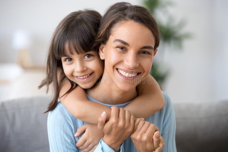 Mamá feliz e hija linda del niño que abrazan mirando la cámara fotos de archivo libres de regalías