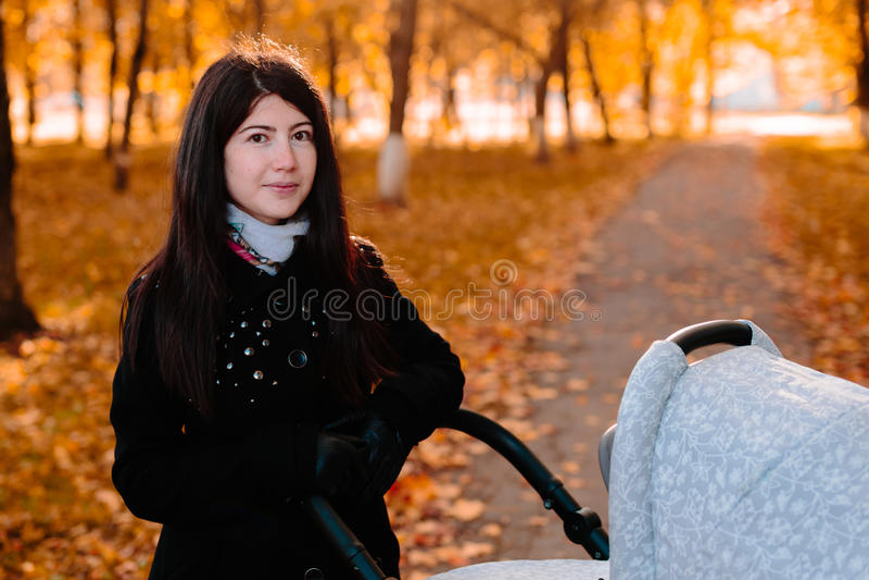 Mamá feliz joven con un cochecito en parque del otoño imagen de archivo
