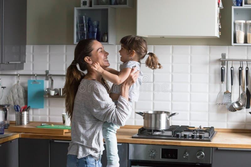 Mamá feliz que lleva a cabo jugar de risa de la muchacha del niño en la cocina imagenes de archivo