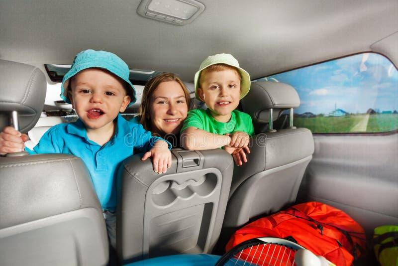 Mamá feliz que se divierte con sus hijos que se sientan en coche imagen de archivo