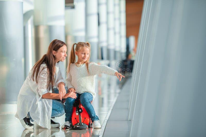 Mamá feliz y niña pequeña con tarjeta de embarque en el aeropuerto imágenes de archivo libres de regalías