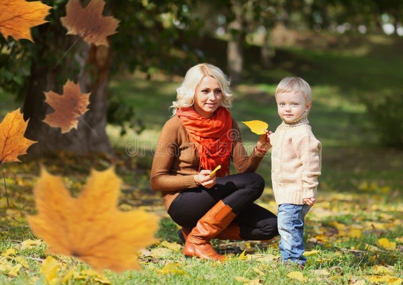 Mamá feliz y niño que juegan junto en día caliente del otoño imagenes de archivo