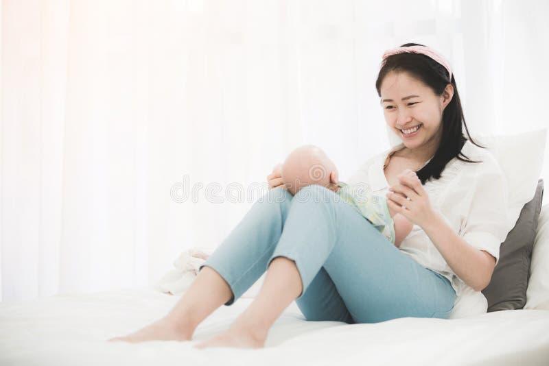Mamá hermosa asiática que juega con su bebé imagen de archivo libre de regalías