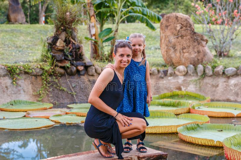 Mamá hermosa con poca hija cerca de la charca de loto en el parque en un día soleado fotos de archivo