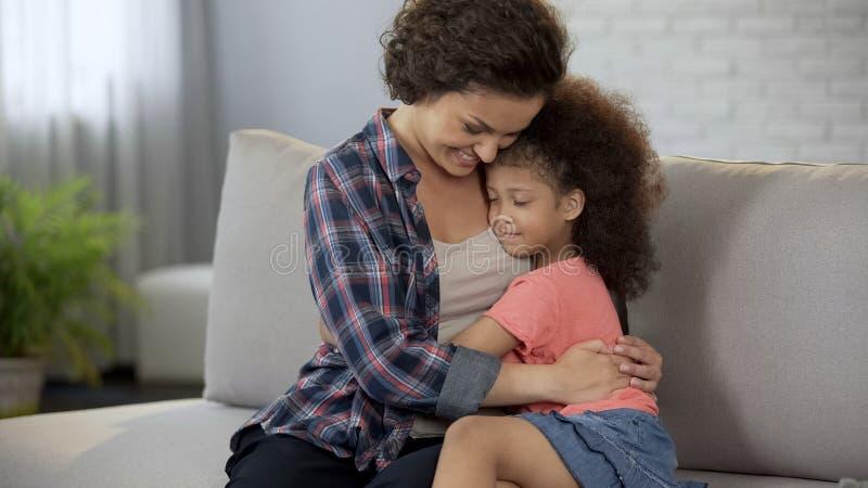 Mamá hermosa que conforta a su pequeña hija y que se calienta con su amor sin fin foto de archivo