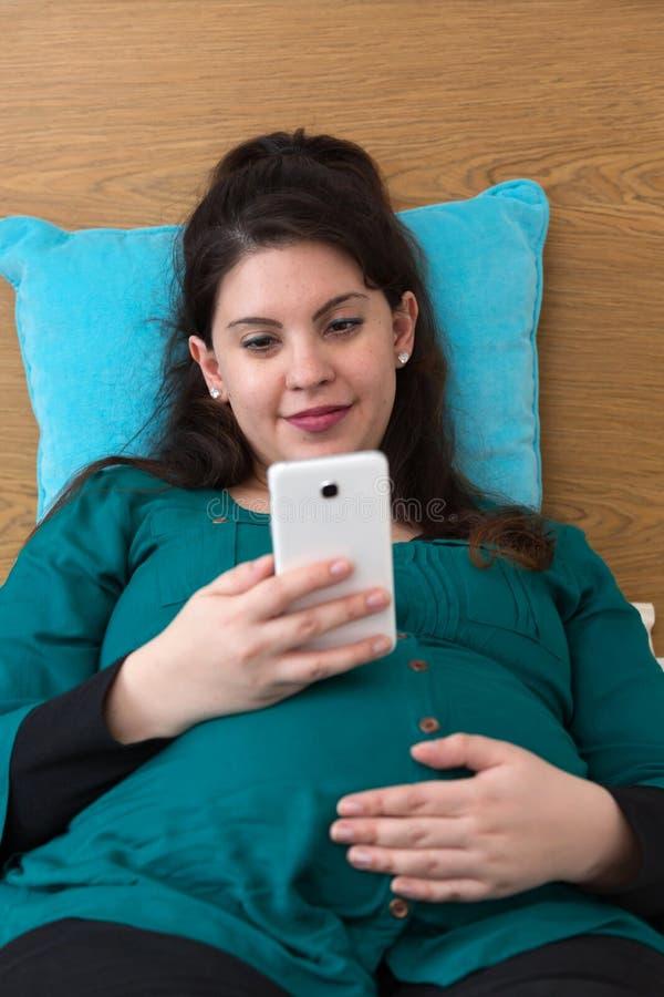 Mamá joven expectante feliz que busca en su Smartphone foto de archivo
