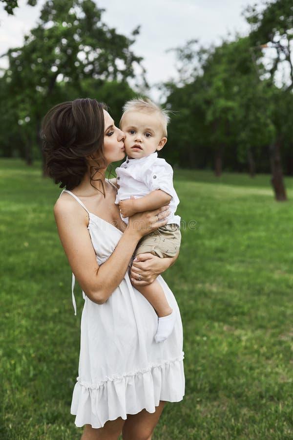 Mamá joven morena hermosa en el vestido elegante blanco corto que se sostiene en sus manos y que besa a su bebé lindo al aire lib foto de archivo libre de regalías