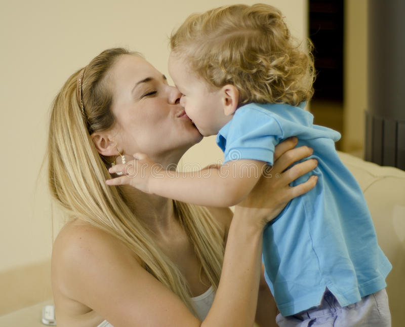 Mamá joven que besa a su hijo fotografía de archivo libre de regalías