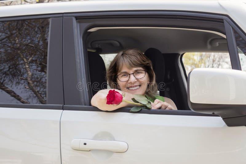 Mamá joven que se sienta en su coche que sostiene una rosa roja imagen de archivo