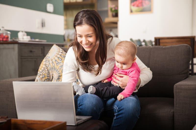 Mamá joven que trabaja en casa con su bebé imagen de archivo