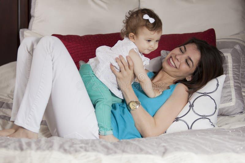 Mamá joven y bebé que se divierten imagen de archivo
