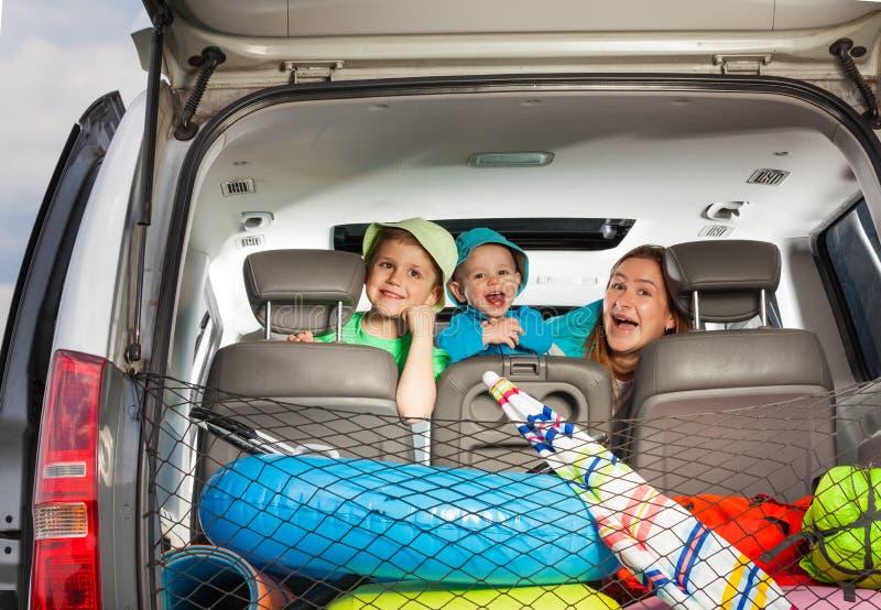 Mamá linda con los hijos que miran a escondidas de detrás un asiento de carro fotografía de archivo libre de regalías