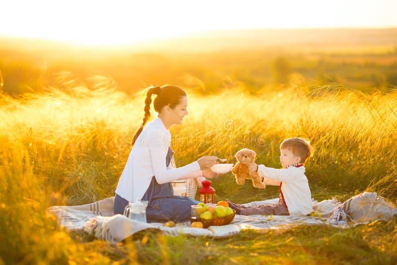 Mamá linda y pequeño hijo que juegan con mi peluche El peluche de alimentación de la madre y del hijo refiere una comida campestr fotos de archivo libres de regalías