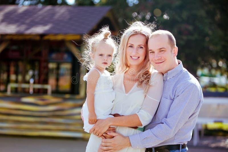 Mamá, papá e hija sonriendo en el verano en el fondo de fotos de archivo