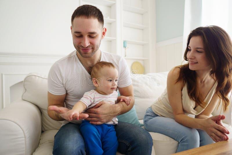 Mamá, papá e hijo divirtiéndose en sala de estar fotos de archivo