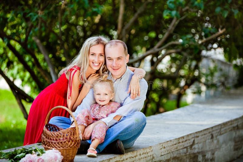 Mamá, papá y muchacha encantadora sonriendo en los árboles del fondo imagen de archivo libre de regalías