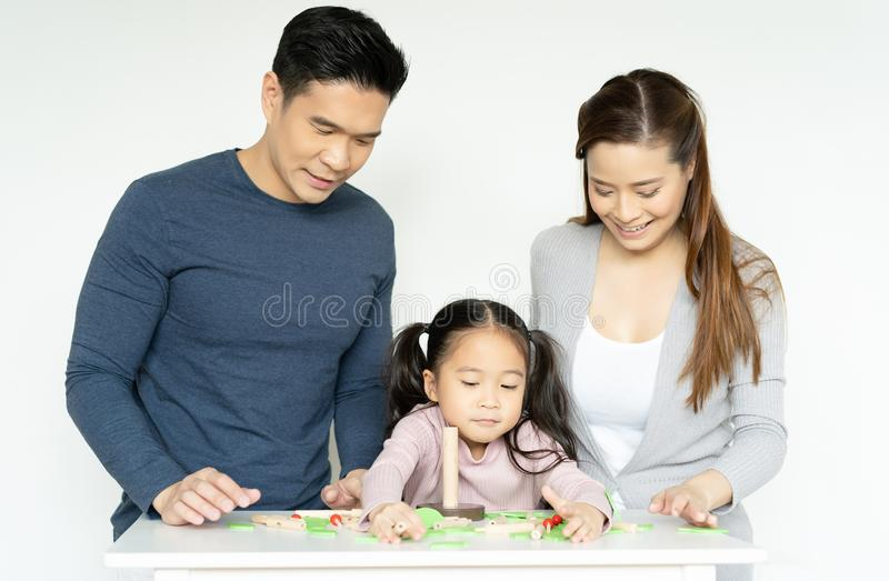Mam?, pap? y muchacha jugando as? como los juguetes de madera en el sitio blanco Hija con infeliz con los padres despu?s de jugar fotos de archivo