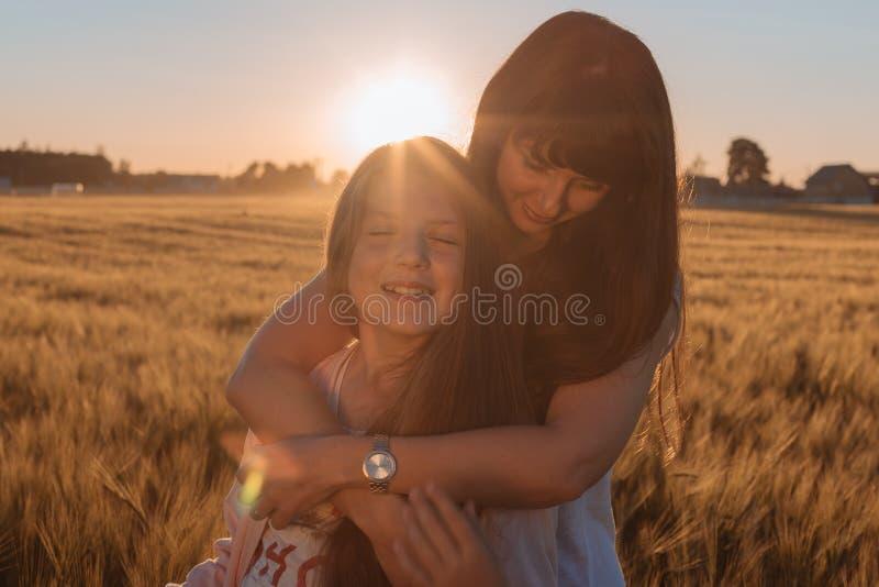 Mamá que abraza a su hija en el campo amarillo imágenes de archivo libres de regalías