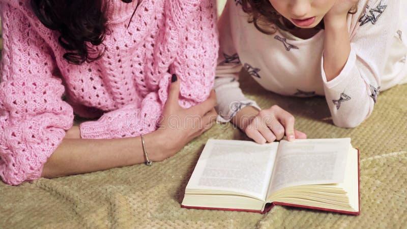Mamá que comprueba la preparación de las hijas en la literatura, padres como profesores particulares, enseñando en casa foto de archivo libre de regalías