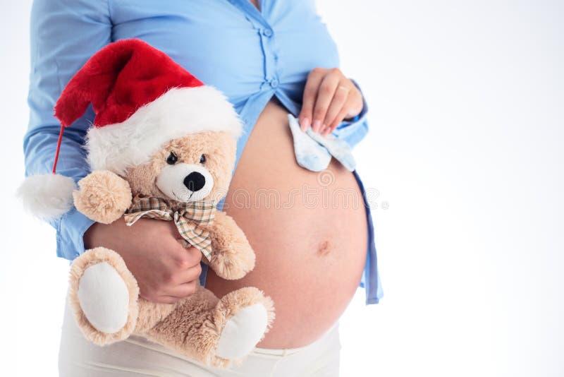 Mamá que cuenta con al bebé Mujer embarazada que lleva a cabo calcetines del bebé azul y f imagenes de archivo