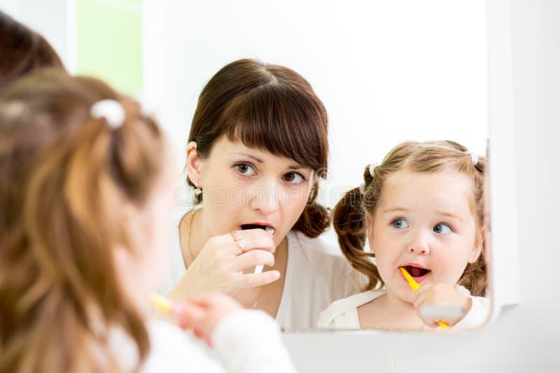 Mamá que da instrucciones el cepillado de dientes del niño foto de archivo