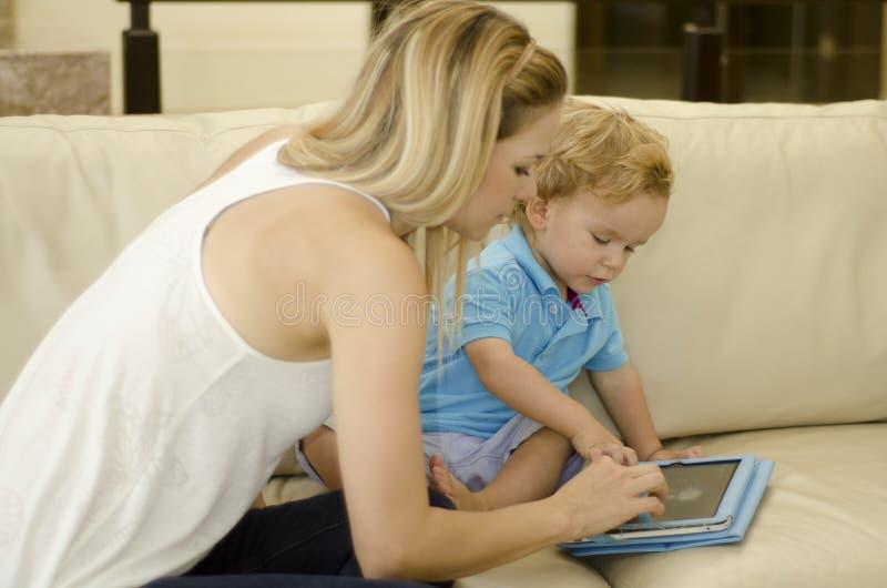 Mamá que enseña a su hijo a utilizar la tableta imágenes de archivo libres de regalías
