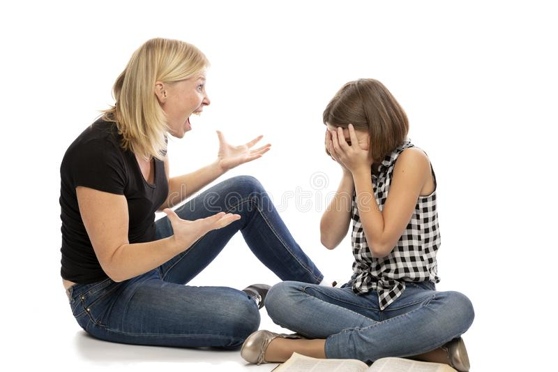 Mamá que grita en la hija adolescente, aislada en el fondo blanco imagen de archivo