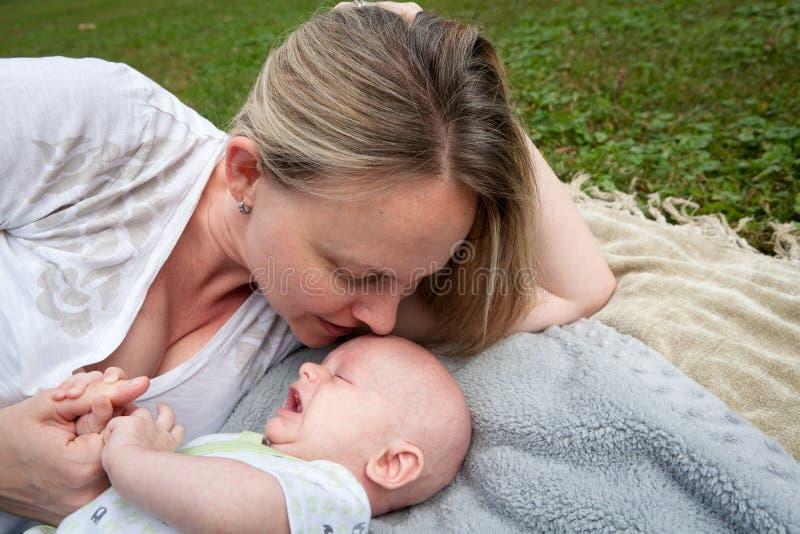 Mamá que habla con el bebé gritador fotografía de archivo