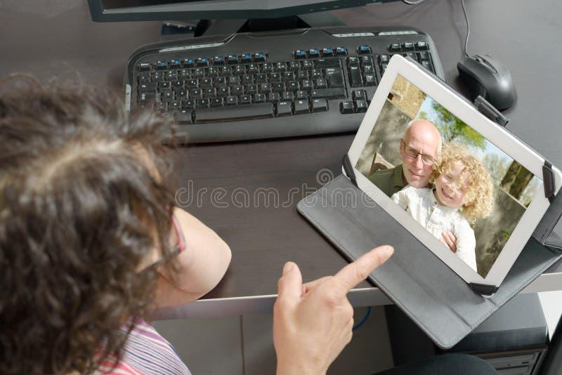 Mamá que hace una llamada distante en Internet imagen de archivo