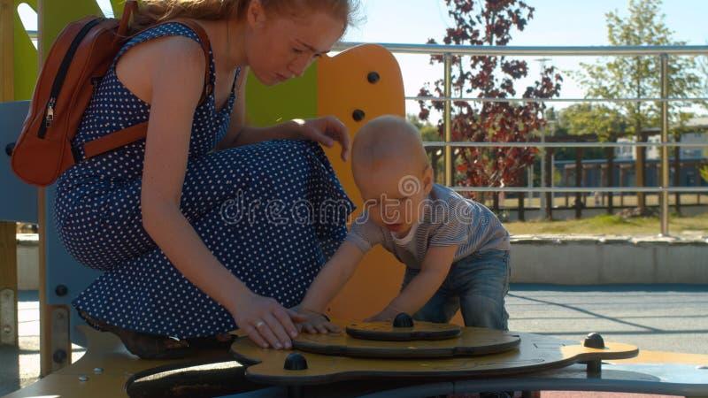 Mamá que juega con el bebé en el parque imagenes de archivo