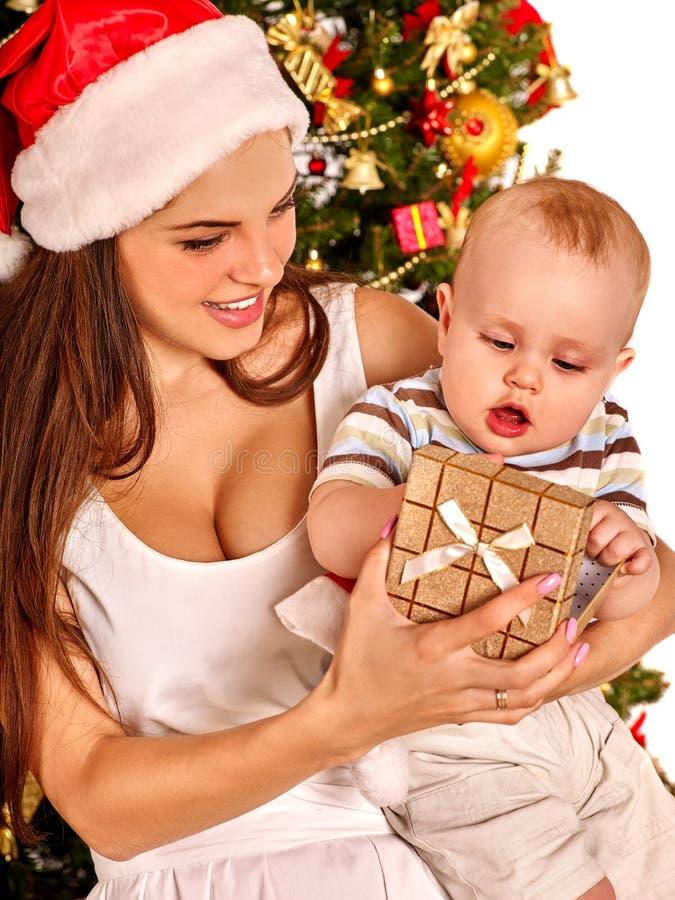 Mamá que lleva el sombrero de Papá Noel que detiene al bebé debajo imagen de archivo libre de regalías
