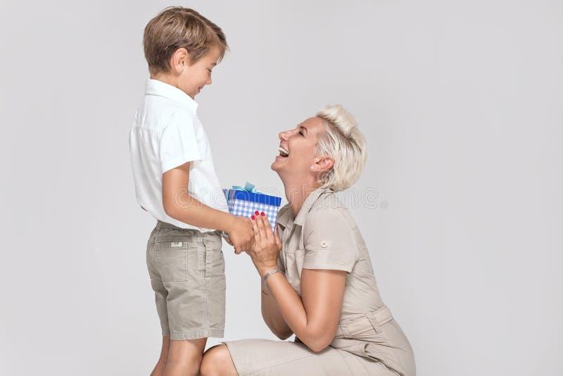 Mamá que presenta con el hijo joven, sonriendo fotografía de archivo libre de regalías