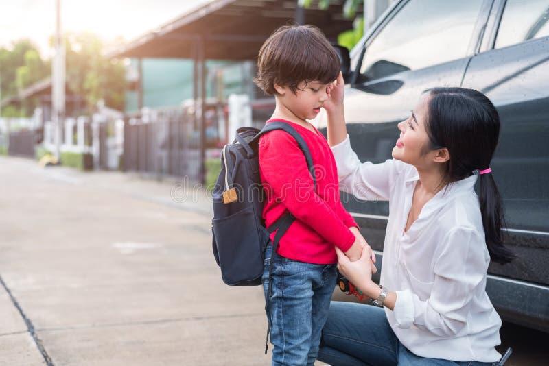 Mamá que se prepara para enviar a sus niños de nuevo a escuela en el coche en mañana foto de archivo
