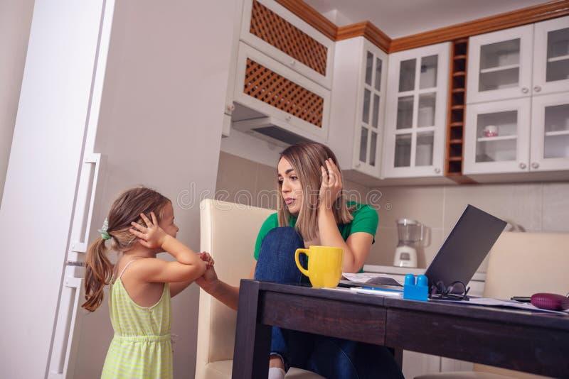 Mamá que trabaja de hogar con el ordenador mientras que se ocupa su daug imagenes de archivo