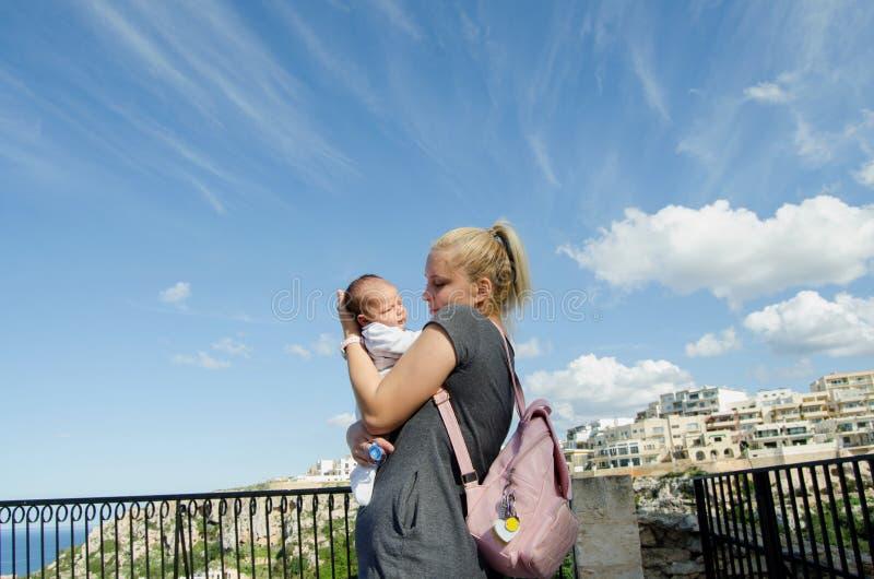 Mamá rubia joven que detiene a un viejo bebé del mes, cielo azul, día soleado fotografía de archivo