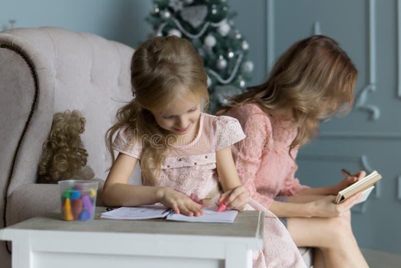 Mamá rubia joven que se sienta en el sofá en planes rosados de la escritura de la blusa Árbol de navidad Imágenes de los raws de  imagen de archivo