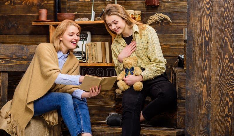 Mamá y adolescente que miran a través de álbum viejo de la familia Mujer y su hija que sonríen mientras que libro de lectura, fel imagen de archivo