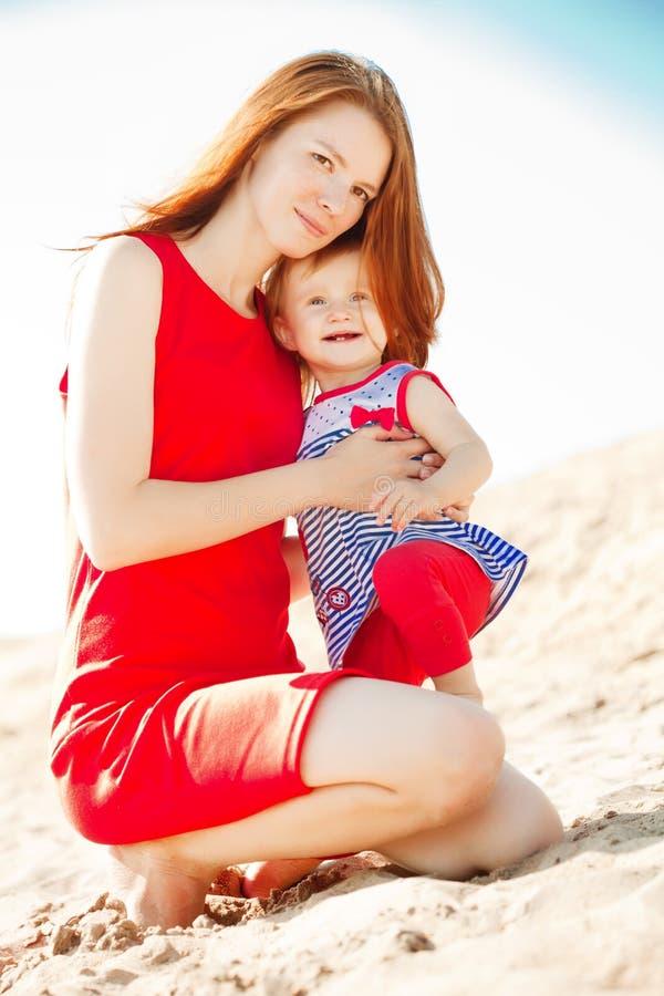 Mamá y bebé hermosos al aire libre Familia feliz que juega en el bea imagen de archivo
