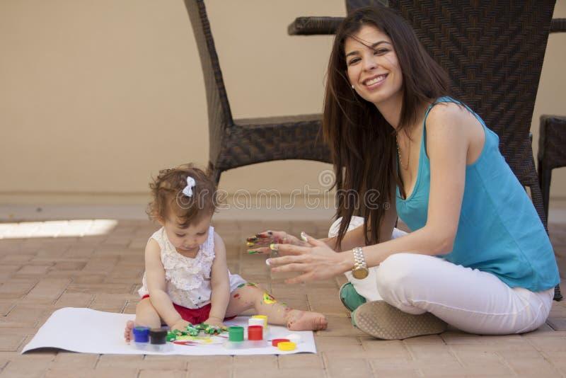 Mamá y bebé que pintan al aire libre fotografía de archivo libre de regalías