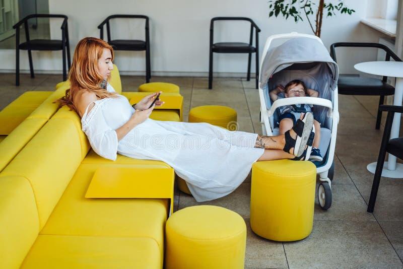 Mamá y cochecito con su bebé imagen de archivo libre de regalías