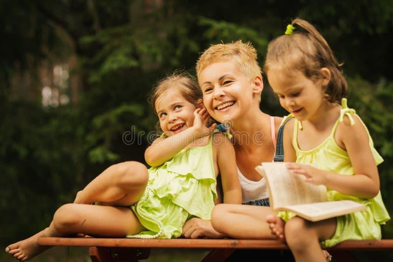 Mamá y dos hijas adorables que presentan en una mesa de picnic en un bosque del verano foto de archivo libre de regalías