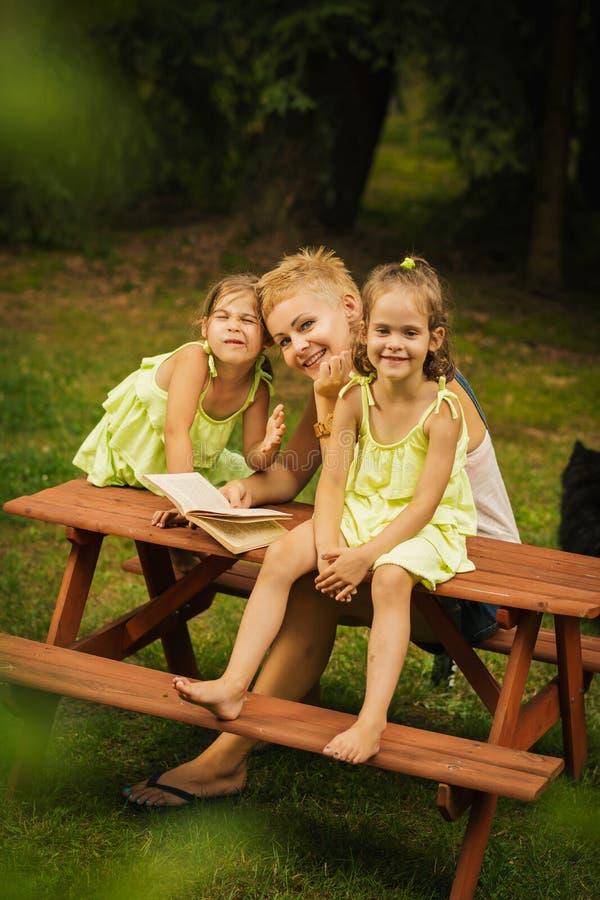 Mamá y dos hijas adorables que presentan en una mesa de picnic en un bosque del verano fotografía de archivo
