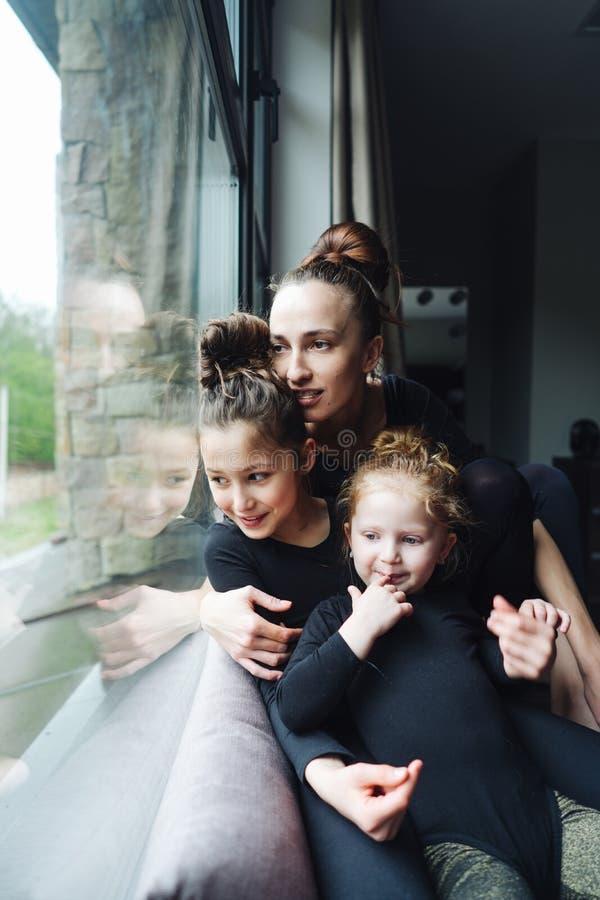 Mamá y dos hijas junto en la ventana imágenes de archivo libres de regalías