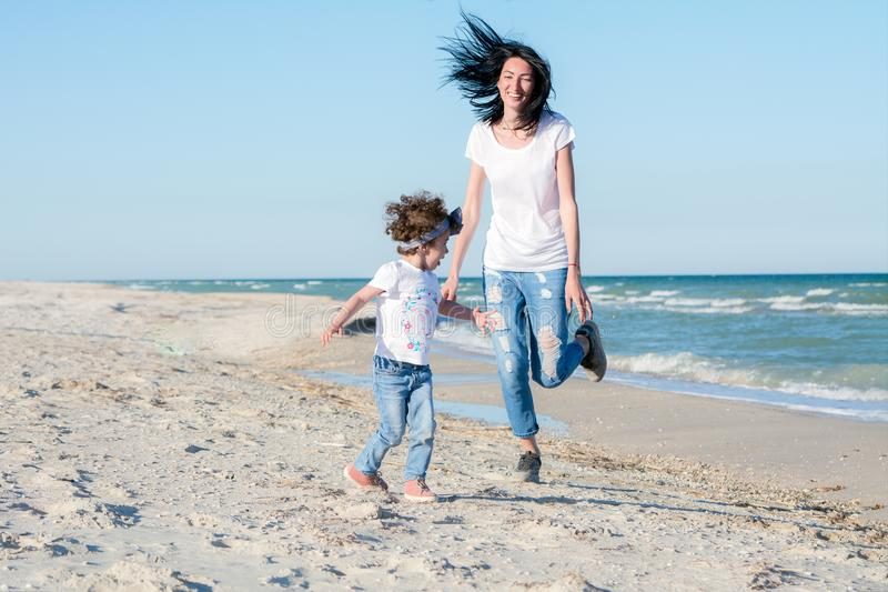 Mamá y doughter en la playa, divirtiéndose junto imagenes de archivo