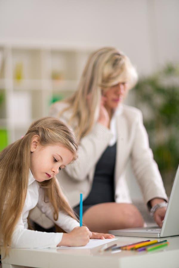 Mamá y empresaria en casa con la hija imagen de archivo libre de regalías