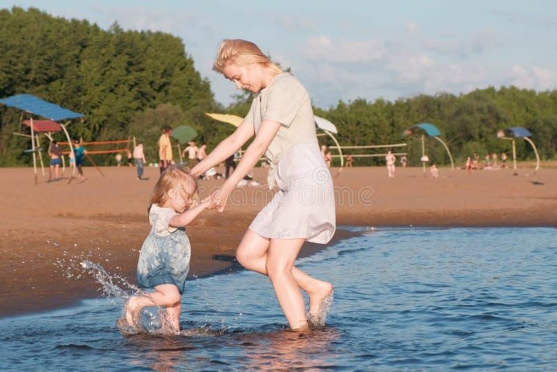 Mamá y muchacha que juegan en la playa del río en la puesta del sol y la nadada imagenes de archivo