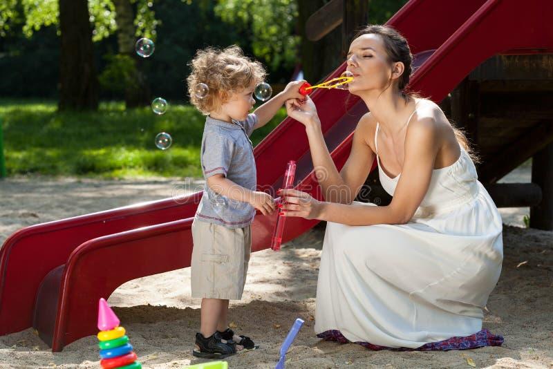 Mamá y muchacho que hacen burbujas imagen de archivo